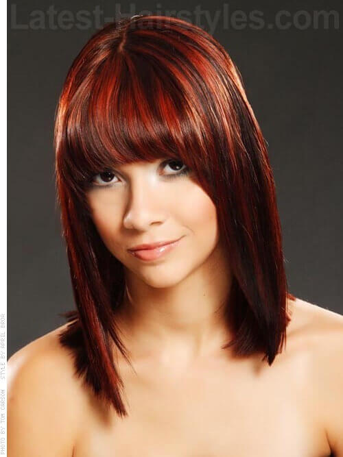 A red sleek shoulder length hairstyle with blunt bangs