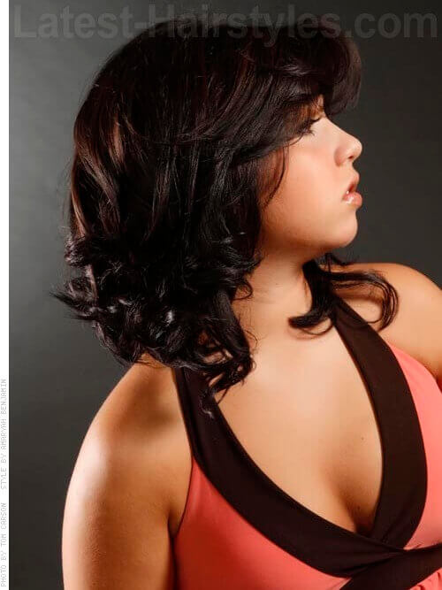 Shoulder length curly hairstyle with bangs side view