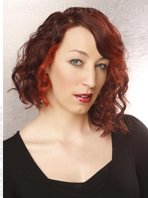 A popular asymmetrical cut with cranberry red hair color