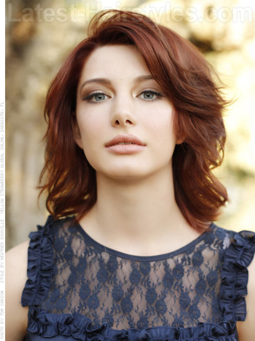 A medium length layered haircut with auburn red hair color