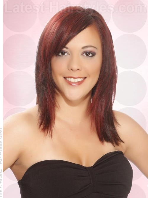 Layered medium length haircut with red highlights