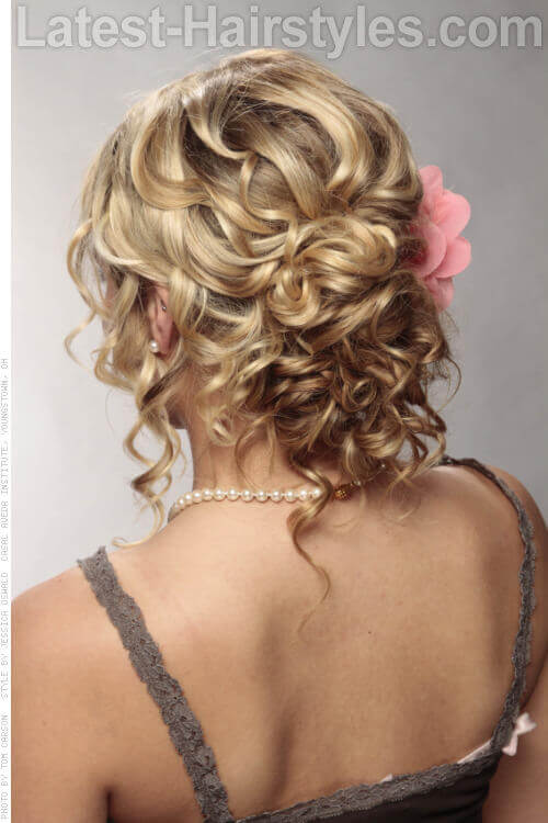 24 completely easy long hair updos for you to try curly updo with flower accessory back view pmusecretfo Choice Image