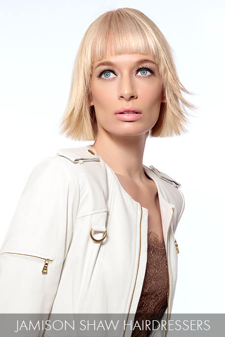 A Bluntly Cut Champagne Blonde Bob With Bangs Is A Modern
