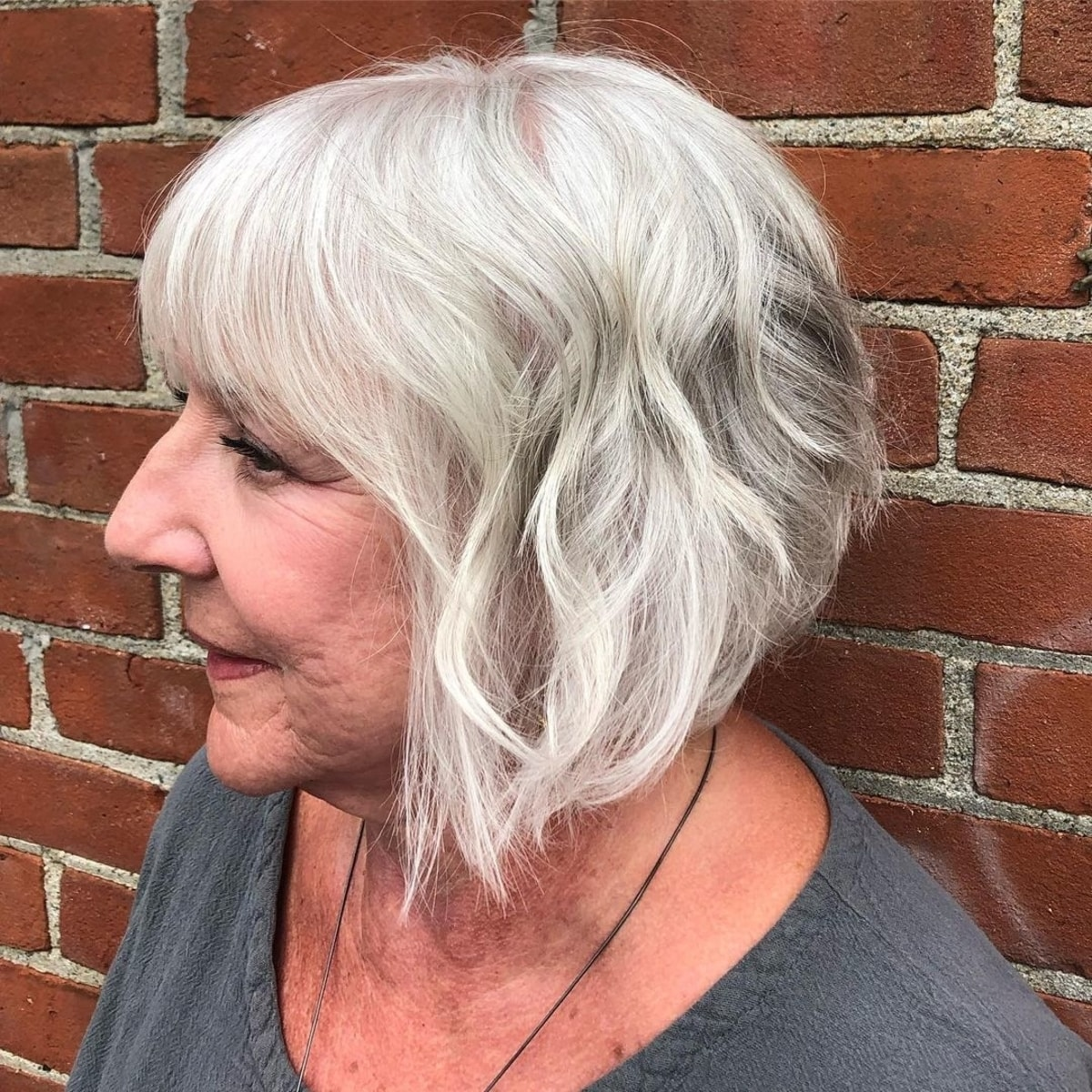 Bob en ángulo favorecedor para cabello gris con flequillo completo