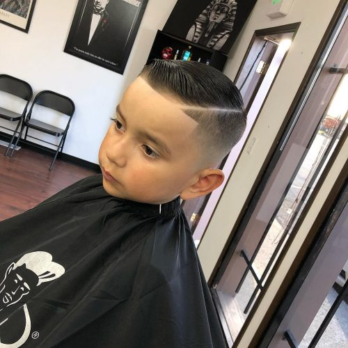 A boys quiff hairstyle with a bald fade