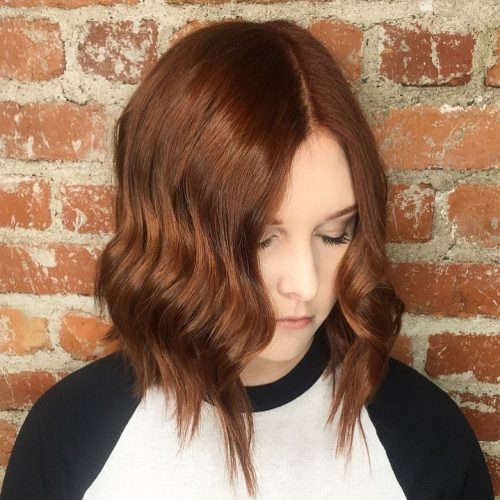 A brick red hair color with a middle part