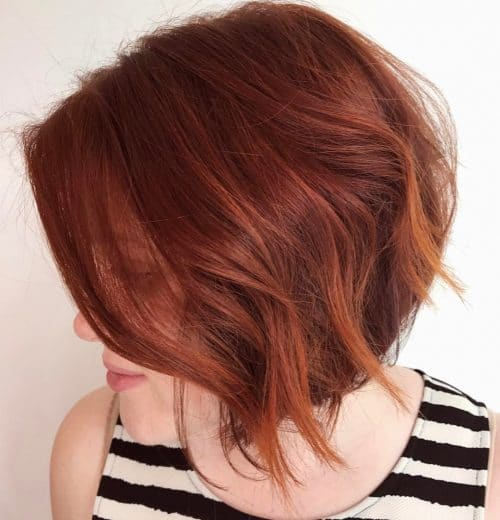A chin length layered bob haircut with red hair color