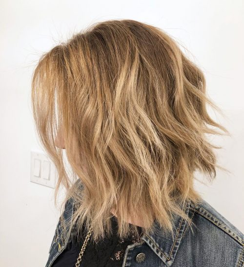 A frizzy shoulder length haircut with waves