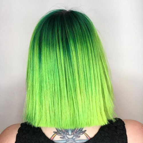 An edgy dark to light green ombre medium length bob