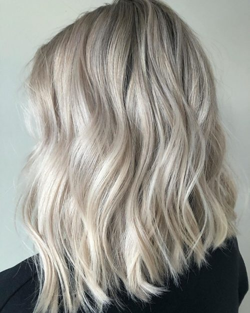Rubia de hielo con cabello largo hasta los hombros con estilo ondulado de playa