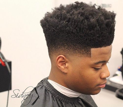 Low skin fade haircut with a hightop and curly twist