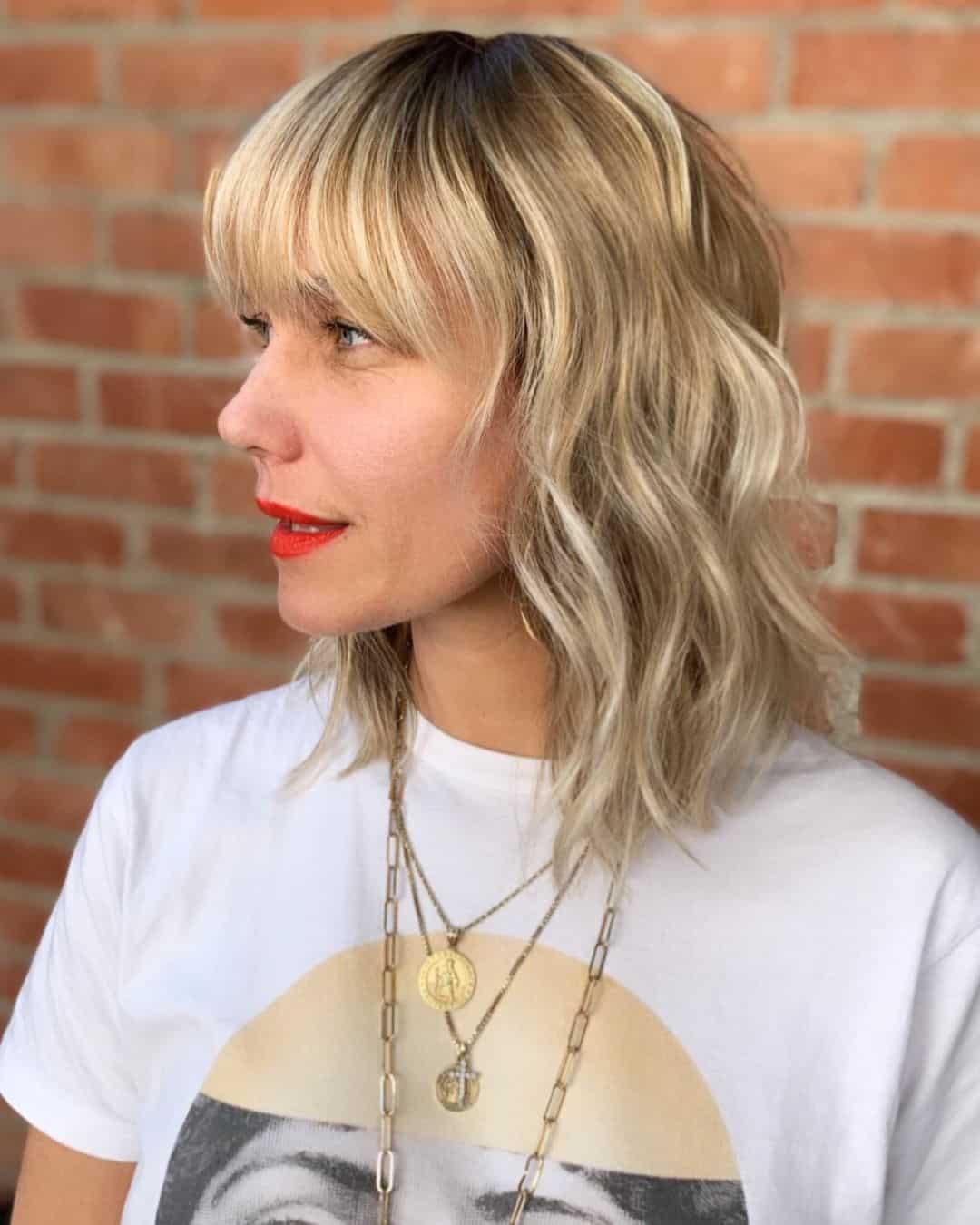 medium length icy blonde wavy bob with bangs