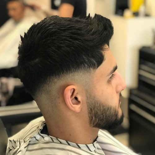 Corte de pelo de longitud media y barba con desvanecimiento hasta la mitad