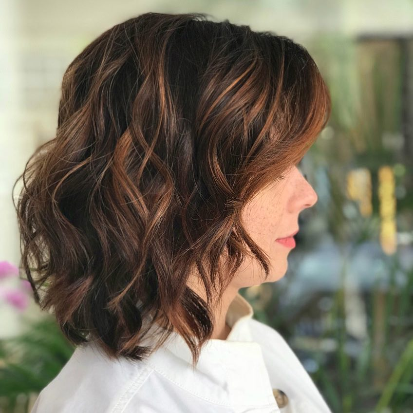An enchanting brunette medium length bob with auburn highlights