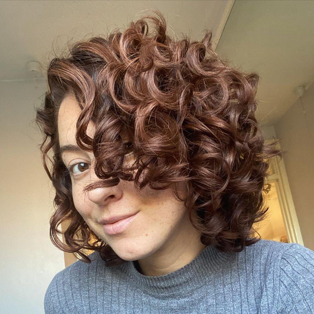 Corte de cuello para cabello castaño rizado