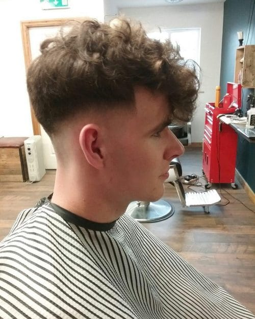 An old-school fade cut with curly fringe