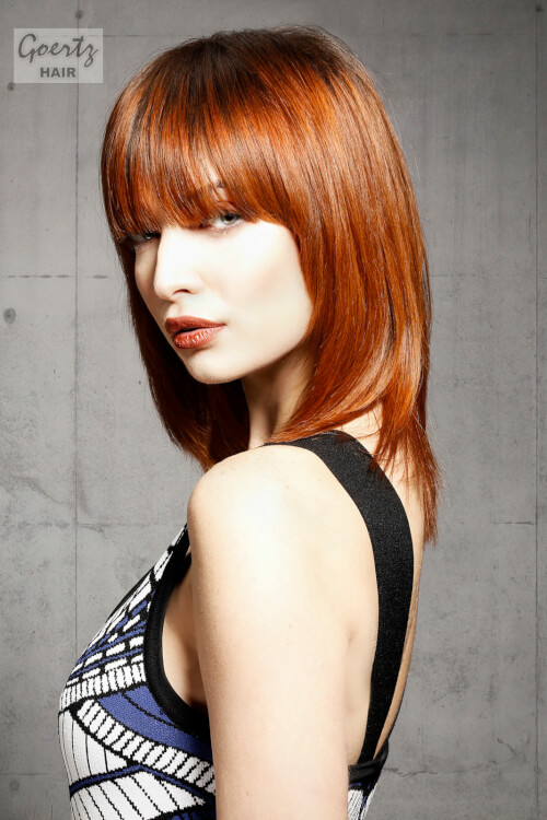 A Bold And Bright Copper Red Hair Color With Bangs