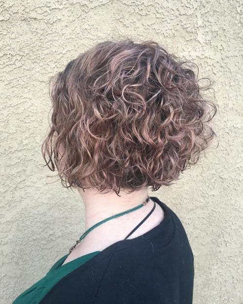 A curly bob with rose gold highlights