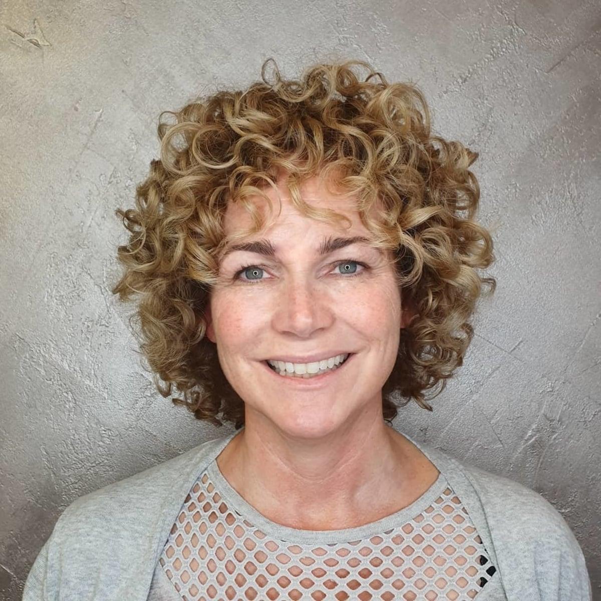 Peinado corto y rizado para mujeres mayores de 50 años.