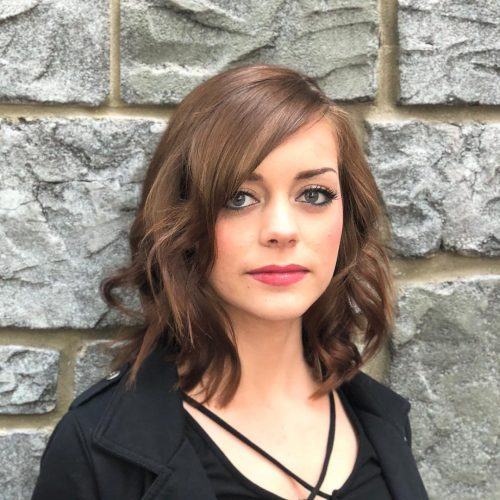 A medium length layered haircut with side fringe