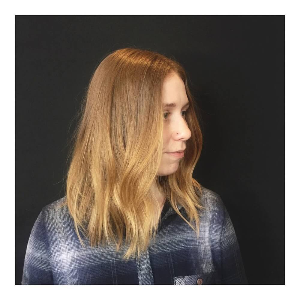 A light brown strawberry blonde lob