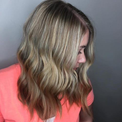 An attractive mid shoulder length cut with beachy waves and bronde hair color
