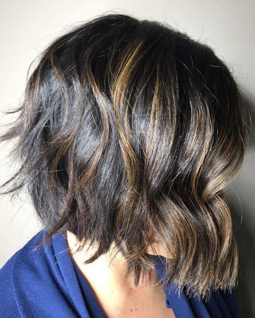 A short neck length layered bob haircut with caramel highlights