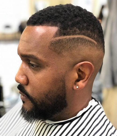 Corte de pelo con línea y desvanecimiento medio con una línea en el cabello