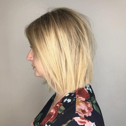 A medium layered haircut with blunt edges and blonde hair color