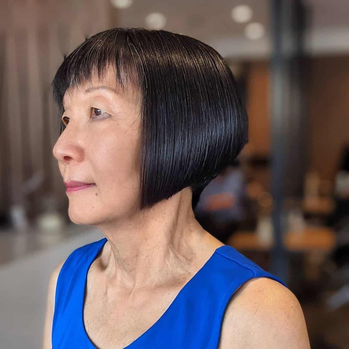Bob muy corto con flequillo para mujeres de sesenta años con cabello lacio