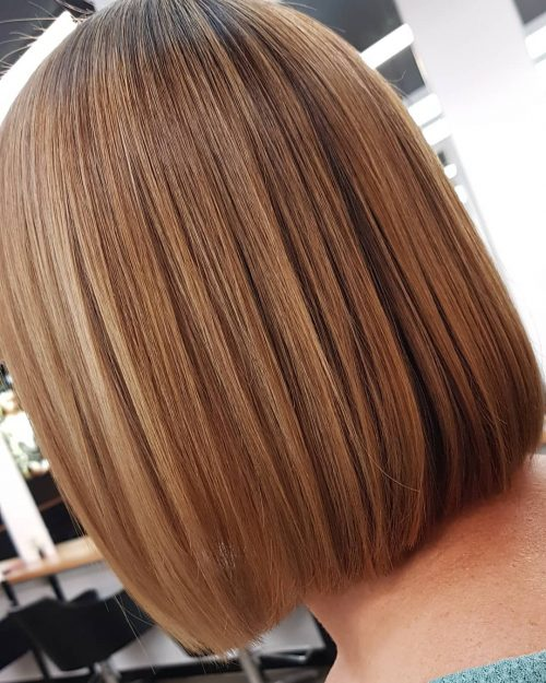 A blunt lob cut with warm honey brown hair color